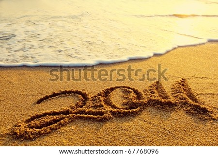Year 2011 date written on the sand of a beach