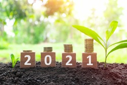 Year 2021 economy growth and recovery, increase money saving and investment concept. Wooden blocks 2021 with increasing stack of coins at sunrise on natural background.