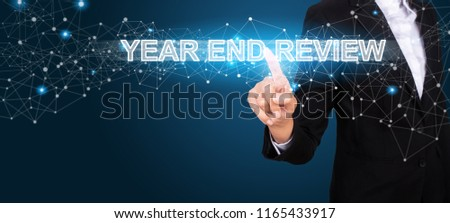 Year End Review concept with Hand of business pressing a button Year End Review. #1165433917