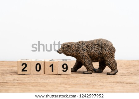Year 2019 financial, equity or stock investment bear market concept with bear figure waking with stack of cube block building year number 2019 on wooden table white background with copy space.