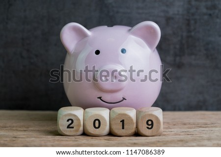 Year 2019 financial goal, happy smiling pink piggy bank with wooden cube block with number 2019 on table and dark black background. #1147086389