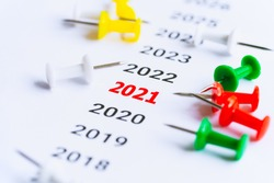 Year 2021 with red push pins written on paper. concept for business vision and business strategy. success concept. transport and travel topics.