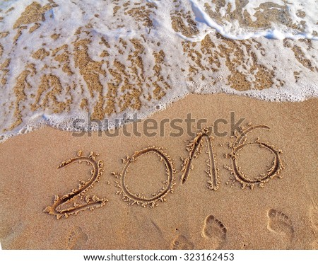Year 2016 written in the sand and wave on a beach #323162453