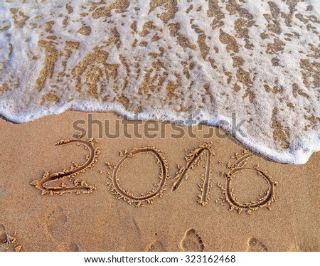 Year 2016 written in the sand on a beach #323162468