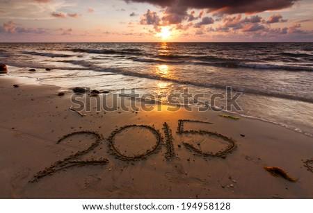 Year 2015 written on sand at sunset