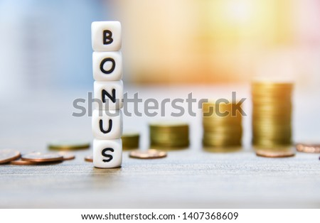 Yearly Bonus concept / words of Bonus and Stack coins on background for Encouragement Morale on the table office company