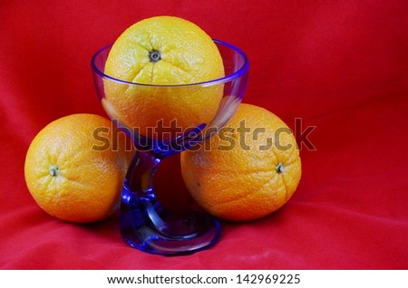 Yelliow Oranges with a Blue  Glass on a Red Bsckground
