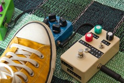 Yello canvas boot hitting a blue guitar pedal on a green plaid carpet , white DIY pedal on the right both connected
