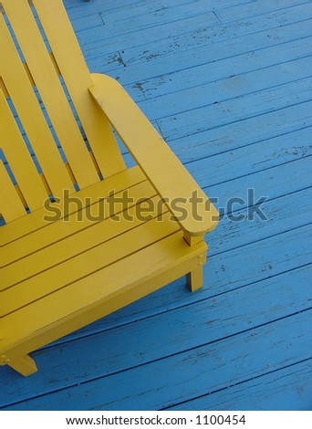 Yellow adirondack chair on blue deck - stock photo