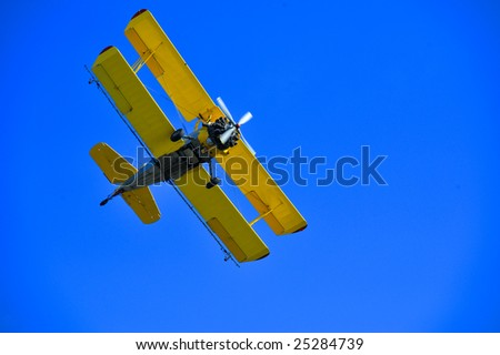 Yellow agricultural airplane on clear blue sky
