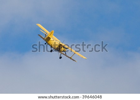 Yellow airplane (biplane) flying in a blue sky.