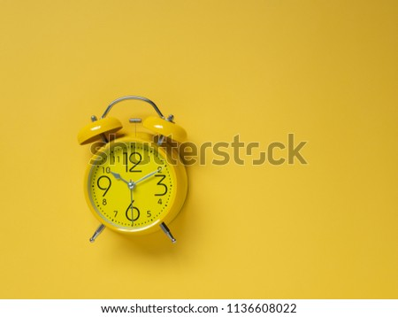 Yellow alarm Clock analog classic retro style on yellow background, Top view and copy space.