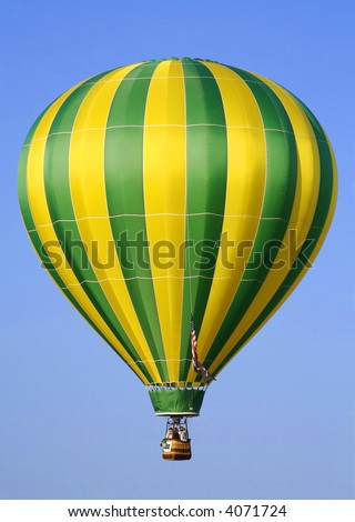 Yellow & Green Striped Hot Air Balloon Lifting Off - stock photo