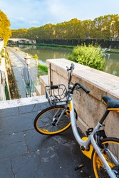 Yellow and black bicycle/ bike with empty front mounted pannier rack/ metal basket parked on street above Tiber River in Rome, Italy. Scenic outdoor landscape view in the historic Roman/ Italian city.