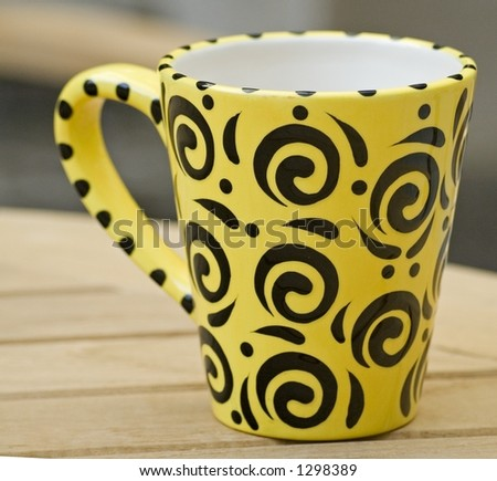 Yellow and black coffee mug on a wooden table in a garden.
