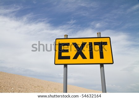 Yellow and Black Exit Sign against a cloudy and blue  sky and pebble beach