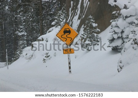 Yellow and black road signs warn of hazards due to slick and icy roads after a severe winter storm, Highway 88, Alpine County CA USA.
