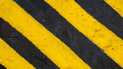 Yellow and black strip paint on road surface; asphalt road texture sign