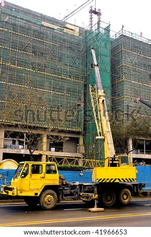Yellow and black telescopic crane are lifting heavy weight on construction site.