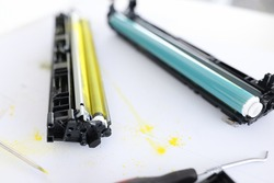 Yellow and blue cartridges for printer lying on table closeup. Repair and refilling of cartridges concept
