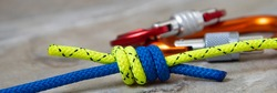 Yellow and blue ropes connected by knot knot on a background of carbines. Double fisherman's or  Grapevine. Climbing knots: double fisherman's grapevine knot. Friendship concept.