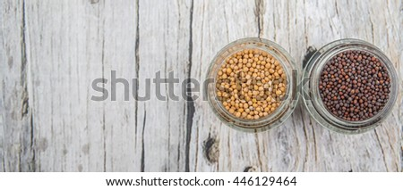 Yellow and brown indian mustard seed in mason jar over wooden background