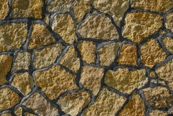 Yellow and brown uneven stone wall texture