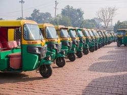 Yellow and green auto rickshaws in Indiya.