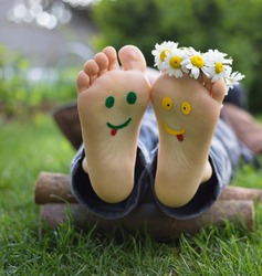 yellow and green faces are painted on the bare feet of a child lying on the grass. Chamomile flowers, green grass, joy, cheerful positive atmosphere, happy childhood. Hello summer, Smile Day