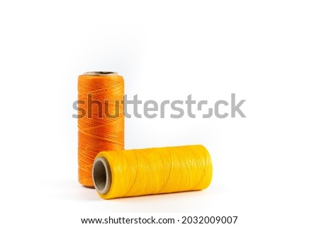 Yellow and orange spools of thread on a white background. Waxed orange and yellow threads for leather products. Yellow thread. Orange thread. Сток-фото ©