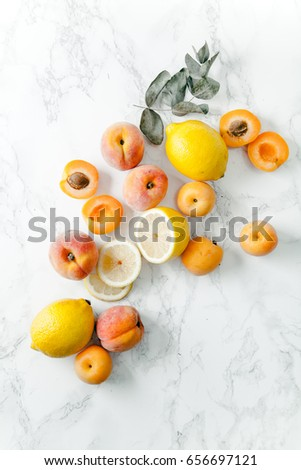 Yellow and orange summer fruits on white marble background. Color food collection concept. Copy space