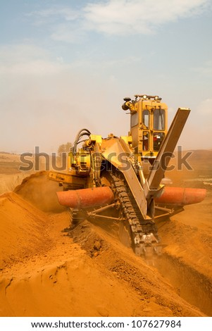 Yellow  and orange Vermeer trencher industrial machine digging trench or ditch outside in red sand or dirt on construction site for new pipe line