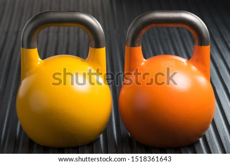 Yellow and orange weight lifting kettlebells inside a gym. Potential copy space on kettlebells.