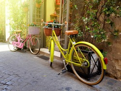 Yellow and pink color bicycles parked on the old street in Rome, Italy