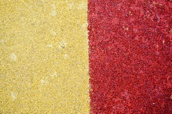 Yellow and red bright soft soft rubber flooring safe for sports and workout or on the playground from the many small round pebbles pressed. Background, texture.