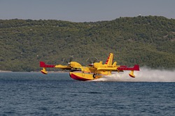 Yellow and red Canadair water bomber, turbo prop firefighting aircraft in action