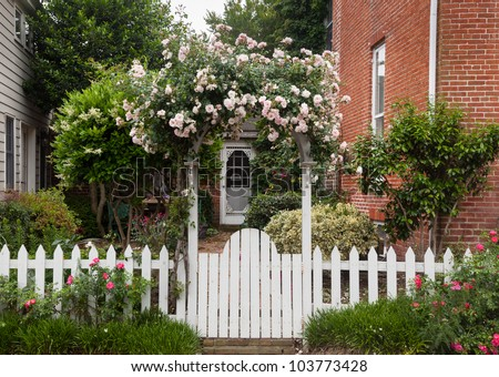 Yellow and red flowers growing along a white picket fence in traditional garden