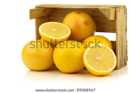 yellow and red grapefruit and a cut one  in a wooden box on a white background