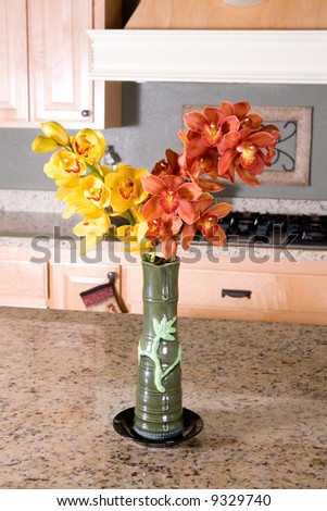 Yellow and red orchid in a vase.