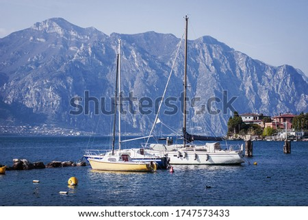 Yellow and white yachts against the backdrop of the mountains on Lake Garda, Malcesine, Northern Italy. Yachts are parked next to bright yellow buoys. Cozy bay, deep blue water, soft evening light.