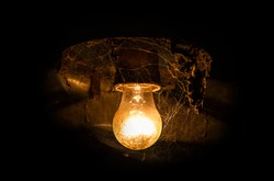 Yellow antique incandescent lamp in the web. Glowing yellow light bulb on a black background.