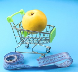 Yellow apple in a miniature supermarket trolley, centimeter tape. Fitness, diet, weight loss concept. Buying healthy products. Side view. Copy space, selective focus