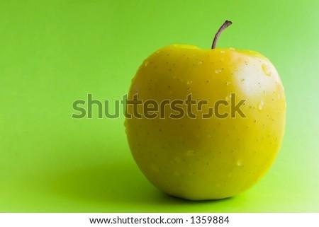 Amarillee la manzana en un fondo verde