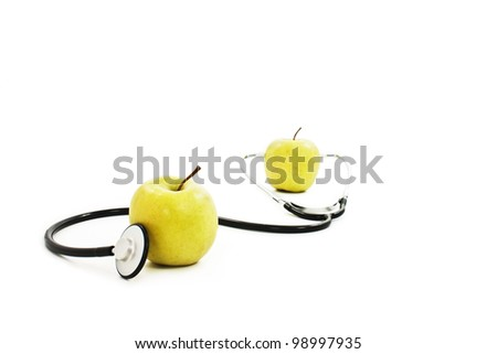 Yellow apples with stethoscope against white background