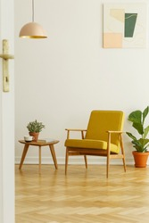 Yellow armchair and coffee table with a cup and plant on a herringbone parquet in a living room interior. Real photo
