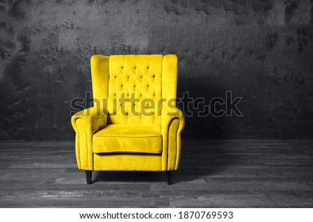 Yellow armchair over grey background. Trendy colors 2021 year.