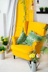 yellow armchair with pillows near the yellow door with a curtain and around them flowers and pots