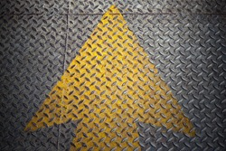 Yellow Arrow paint on steel plate floor
