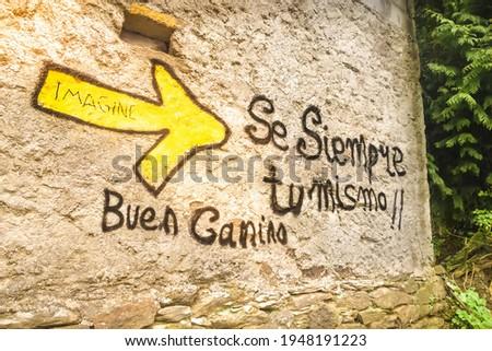 Yellow Arrow Pilgrim Way Mark Sign and Inspirational Writing on Wall along the Way of St James Pilgrimage Trail Camino de Santiago Foto d'archivio ©