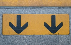 Yellow arrow sign on footway